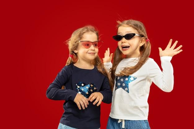 Bella bambina emotiva isolata sullo spazio rosso. ritratto a mezzo busto di sorelle o amici felici in occhiali da sole rossi e neri Foto Gratuite