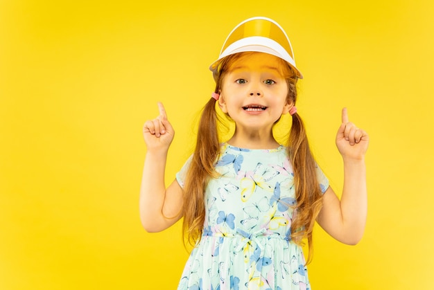 Beautiful emotional little girl isolated on yellow Free Photo