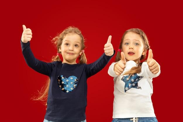 Belle bambine emotive isolate su uno spazio rosso. ritratto a mezzo busto di sorelle o amici felici rivolti verso l'alto Foto Gratuite