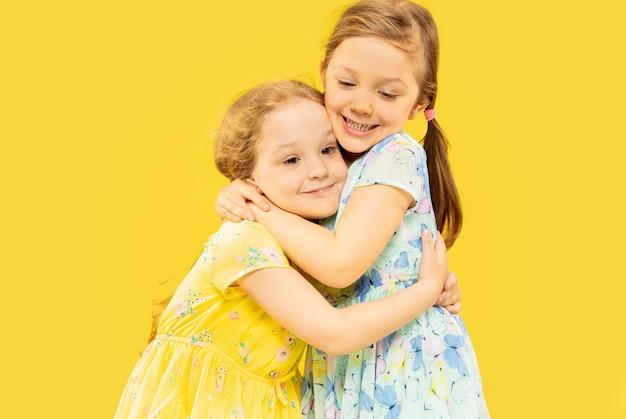 Belle bambine emotive isolate su spazio giallo. ritratto a mezzo busto di due sorelle felici che indossano abiti e si abbracciano Foto Gratuite