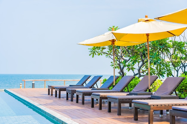 Beautiful empty chairs and umbrellas around outdoor swimming pool in hotel resort Free Photo