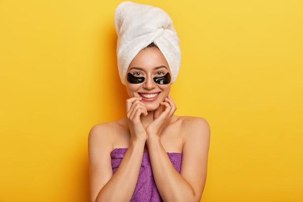 La bella signora europea ha una carnagione giovanile senza rughe, una pelle delicata, applica collagene scuro sotto le macchie degli occhi, ha un trattamento di ringiovanimento, fa la doccia, avvolto in un asciugamano pulito Foto Gratuite
