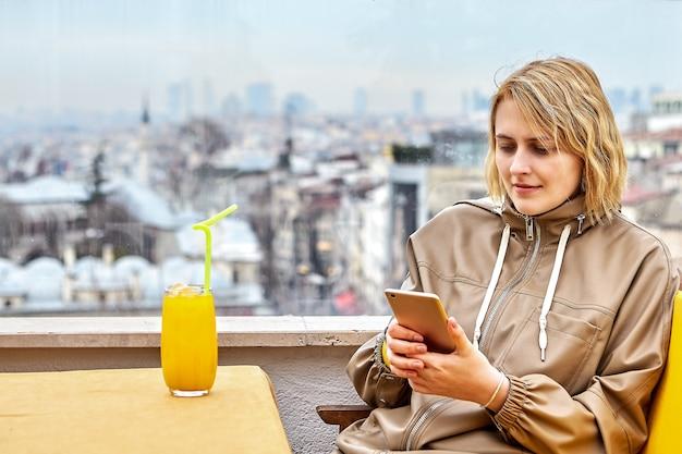 イスタンブールの街並みを見下ろすカフェの窓際のジュースのガラスと20代の美しいヨーロッパの若い女性はスマートフォンの画面でメッセージを読みます。 Premium写真