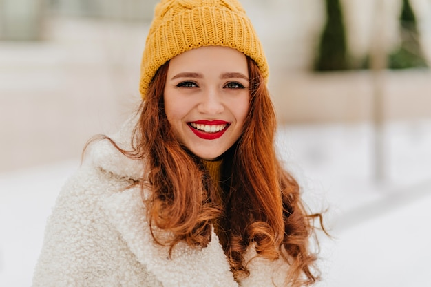 겨울에 웃 고 니트 모자에 아름 다운 유럽 젊은 여자. 세련된 코트에 관능적 인 예쁜 여자의 사진. 무료 사진