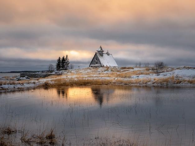 절벽에 황혼에 작은 정통 목조 주택으로 아름 다운 저녁 겨울 풍경. 러시아. 프리미엄 사진
