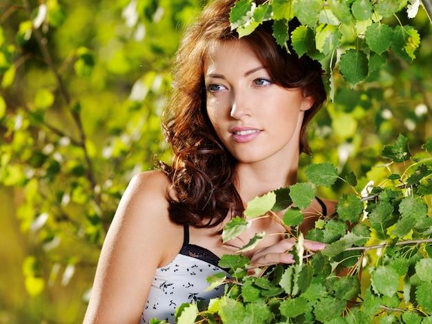 自然の緑の木の近くでポーズをとって若い女性の美しい顔 無料写真