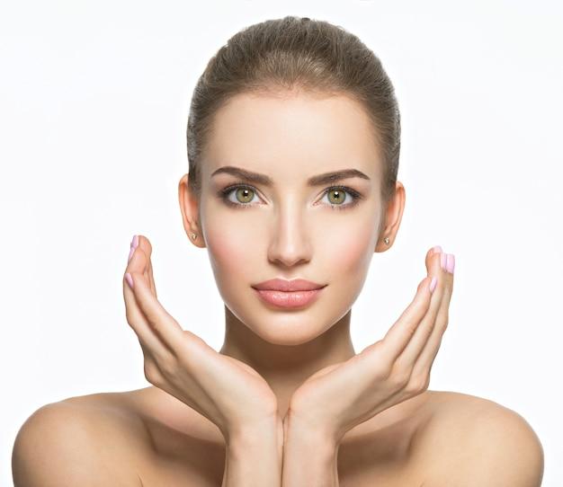완벽 한 건강 피부-흰색 절연 젊은 백인 여자의 아름 다운 얼굴. 스킨 케어 개념. 여성 모델은 얼굴을 만집니다. 무료 사진