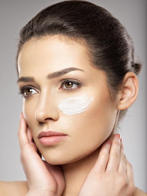 눈 근처 얼굴에 화장품 크림 얼룩을 가진 젊은 여자의 아름 다운 얼굴. 스킨 케어 개념. 미용 치료 개념. 무료 사진
