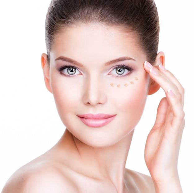 흰 벽에 피부에 화장품 기초와 젊은 여자의 아름 다운 얼굴. 미용 치료 개념. 무료 사진