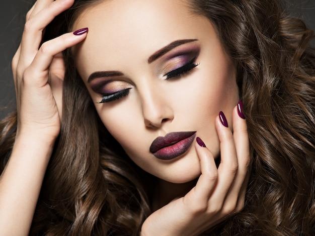 あずき色の化粧をした若い女性の美しい顔。ほのかな唇を持つゴージャスな女の子の肖像画 無料写真