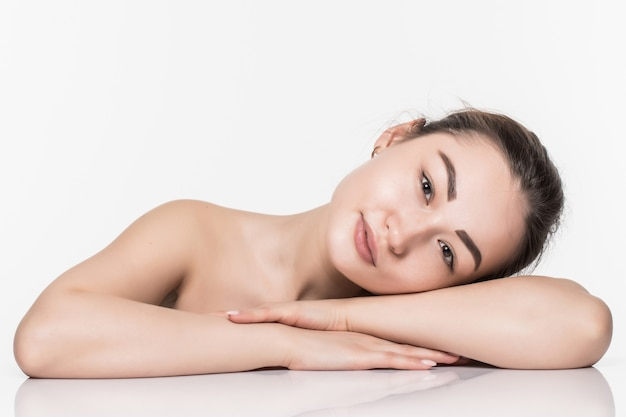 Beautiful face skincare beauty asian woman lying down with mirror reflection isolated on white wall. Free Photo