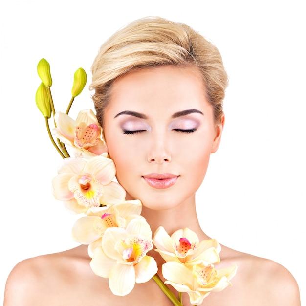 Bel viso di giovane donna graziosa con pelle sana e fiori rosa sul corpo - isolato su bianco Foto Gratuite