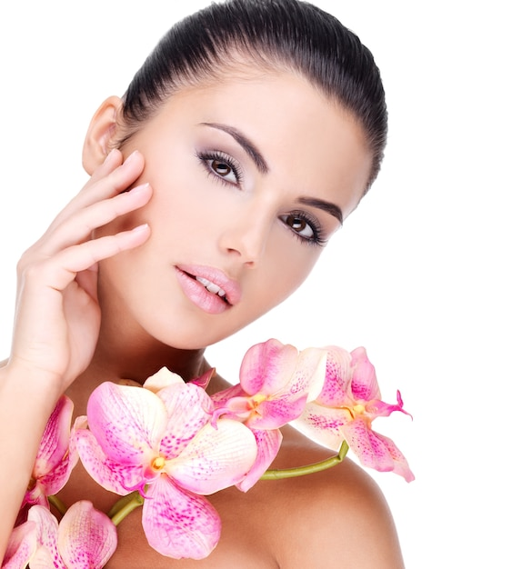 Beautiful face of young pretty woman with healthy skin and pink flowers on body - isolated on white Free Photo
