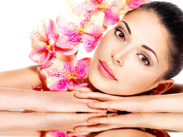 Bel viso di giovane donna graziosa con pelle sana e fiori rosa isolati su bianco Foto Gratuite