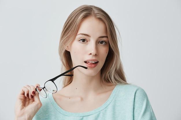 La bella donna pensierosa dai capelli biondi sembra pensierosa da parte con gli occhiali, essendo immersa nei pensieri, analizza qualcosa nella sua mente, Foto Gratuite