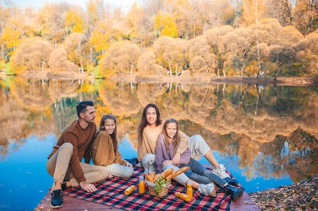 Красивая семья в осенний теплый день возле озера Premium Фотографии