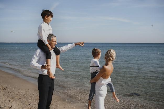 La bella famiglia guarda il paesaggio mozzafiato, genitori e due figli, nella soleggiata giornata estiva Foto Gratuite