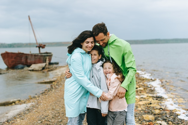 Beautiful family portrait dressed in colorful raincoat near the lake Premium Photo