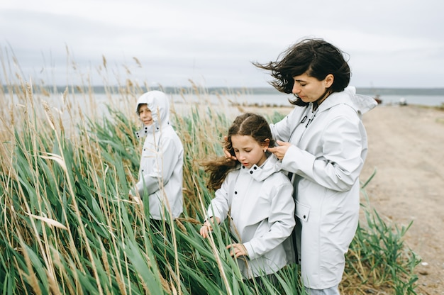 Beautiful family portrait dressed in raincoat near the lake Premium Photo
