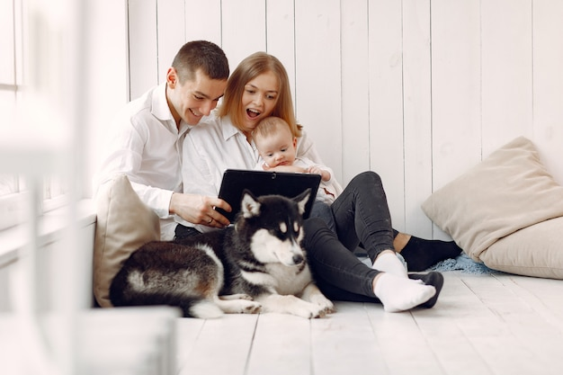 Beautiful family spend time in a bedroom with a tablet Free Photo