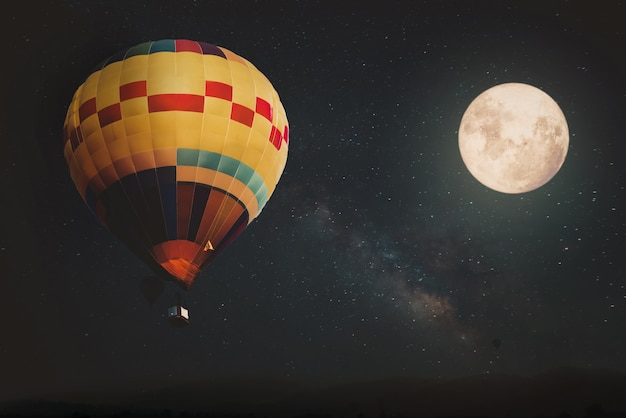 Beautiful fantasy of hot air balloon and full moon with milky way