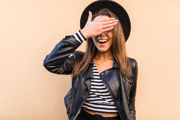 Bella ragazza di moda in giacca di pelle e cappello nero si copre il viso con la mano isolata sul muro giallo chiaro Foto Gratuite