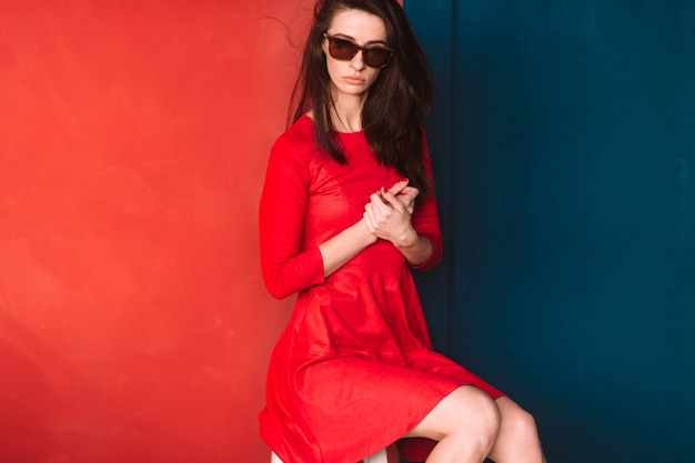 Beautiful fashion girl with dark long hair, spanish appearance in sunglasses and red elegant dress posing on blue red wall. Premium Photo