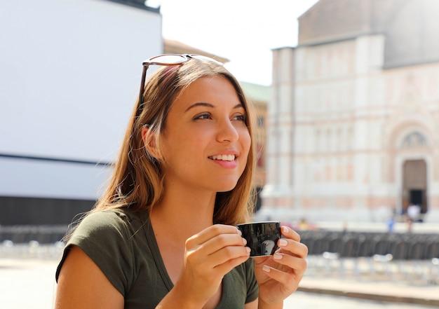 コーヒーを飲みながらイタリアの屋外カフェに座っている美しいファッション女性 Premium写真