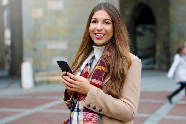 Красивая модная женщина с помощью смартфона, глядя в камеру на улице на улице города Premium Фотографии
