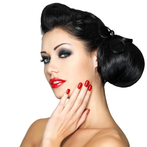 빨간 입술, 손톱 및 창조적 인 헤어 스타일을 가진 아름 다운 패션 여자-흰 벽에 고립 무료 사진