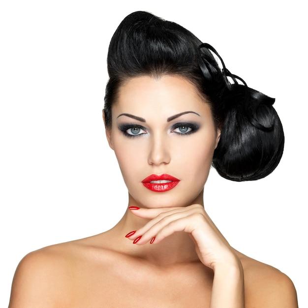 Bella donna di modo con labbra rosse, unghie e acconciatura creativa - isolato sulla parete bianca Foto Gratuite