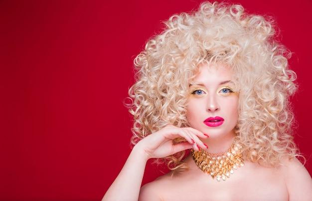 방대한 곱슬 헤어 스타일과 복고 스타일의 아름다운 유행 금발 소녀 프리미엄 사진