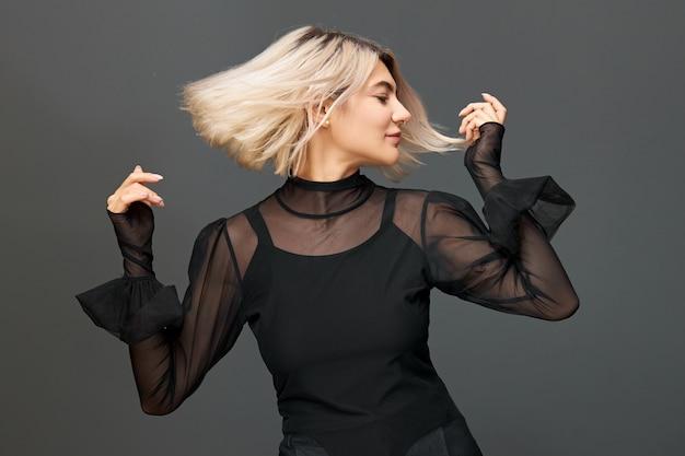 춤을 통해 감정과 감정을 표현하고, 몸을 즐거운 음악으로 옮기고, 웃고있는 염색 머리를 가진 아름다운 유행 젊은 백인 여성. 축제 분위기, 휴식 및 재미있는 개념 무료 사진