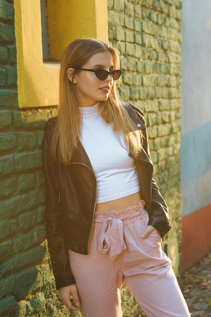 Beautiful fashionable young woman wearing eyeglasses leaning against green brick wall Free Photo