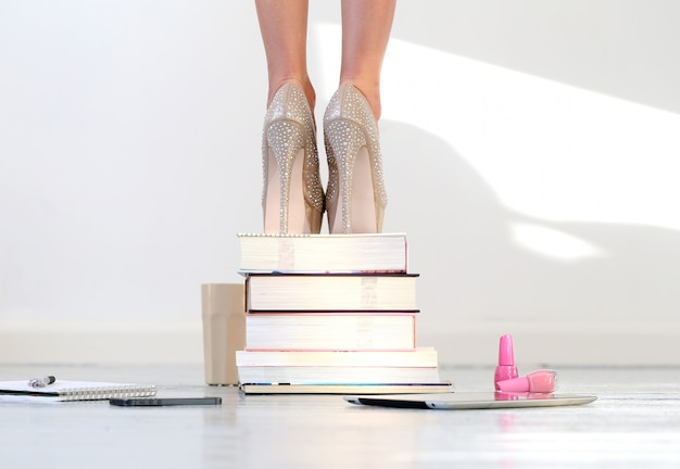 Beautiful feet on stacked books Free Photo