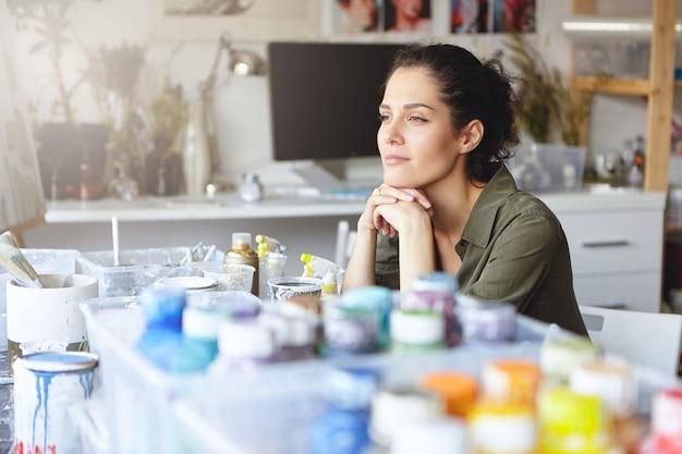 Bella artista femminile con un'espressione pensierosa, seduta nel suo posto di lavoro con gli acquerelli, cercando di immaginare un'immagine che sta per dipingere. persone, hobby, creatività, concetto di pittura Foto Gratuite