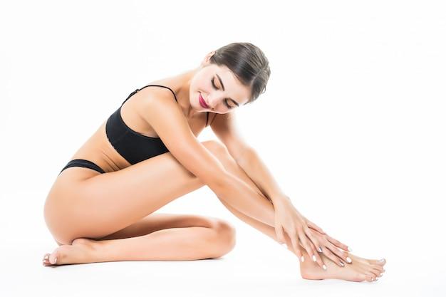 白い壁に分離された美しい女性の身体。床に座って足を手で触れる、美容とスキンケアのコンセプト。 無料写真