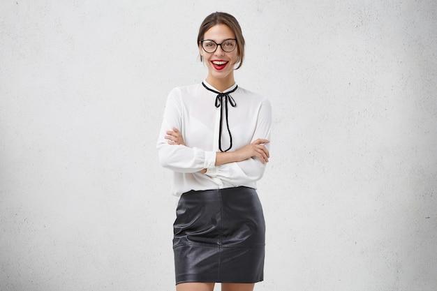 Bella studentessa universitaria indossa abiti bianchi e neri, ha un'occasione speciale, tiene le mani giunte, guarda con sicurezza Foto Gratuite