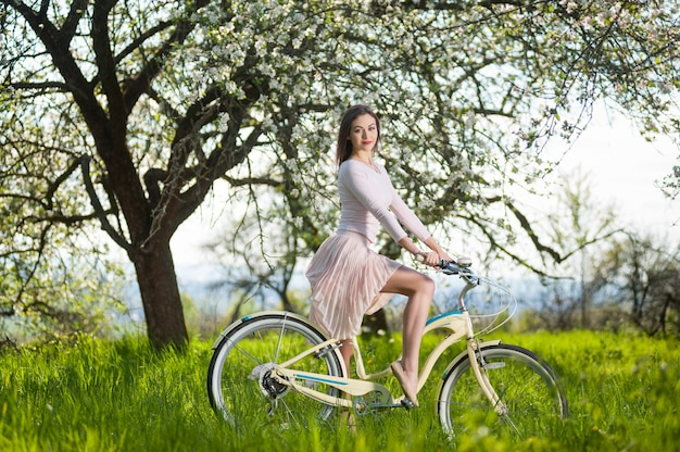 Beautiful female cyclist with retro bicycle in the spring garden Premium Photo