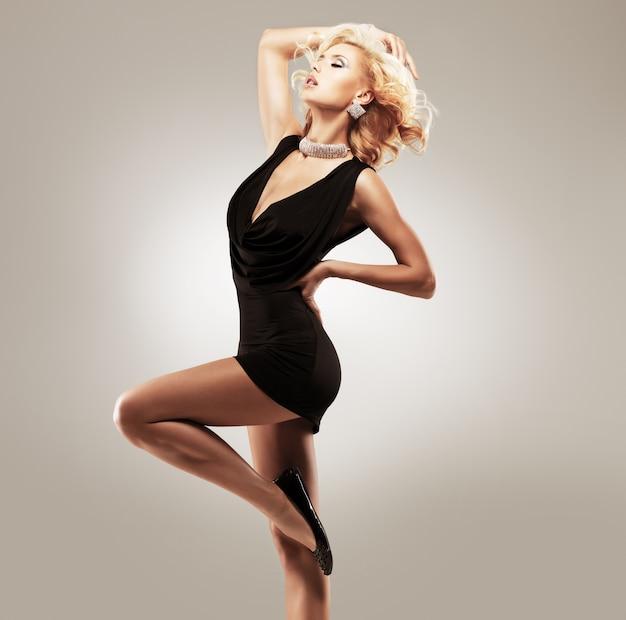 Красивая танцовщица в черном платье позирует в студии Бесплатные Фотографии