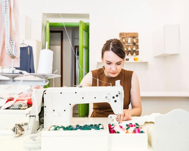 Beautiful female designer sewing fabric on sewing machine Free Photo