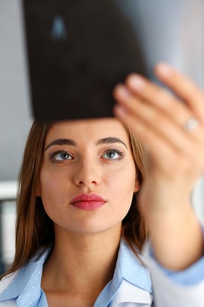 美しい女性医師が腕のx線写真を保持します。 Premium写真
