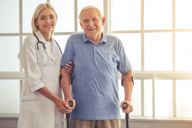 Beautiful female doctor is helping handsome old man. Premium Photo