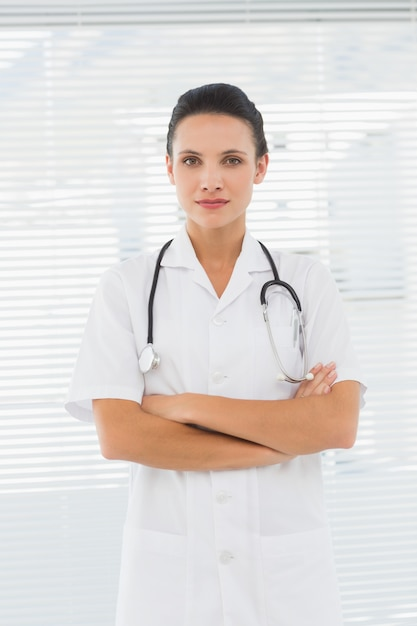 dd781234ebd Beautiful female doctor standing with arms crossed Photo | Premium ...