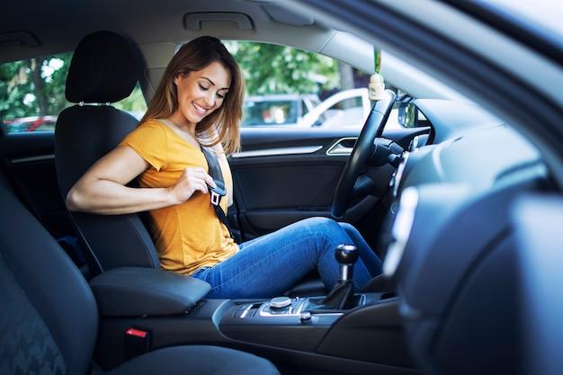 Bello conducente femminile che mette la cintura di sicurezza prima di guidare un'auto Foto Gratuite