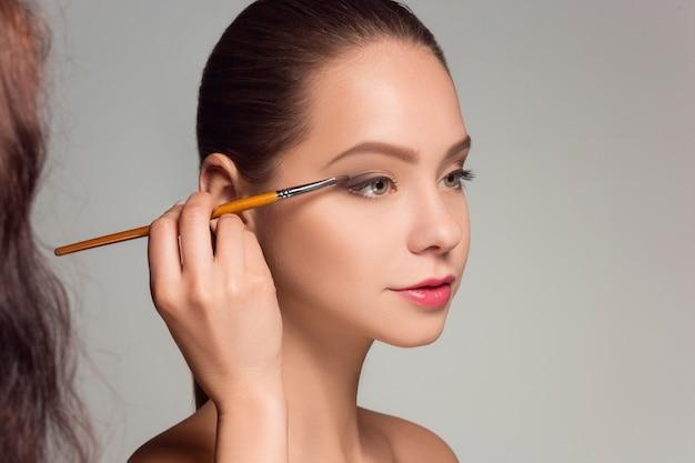 Beautiful female eyes with make-up and brush Free Photo