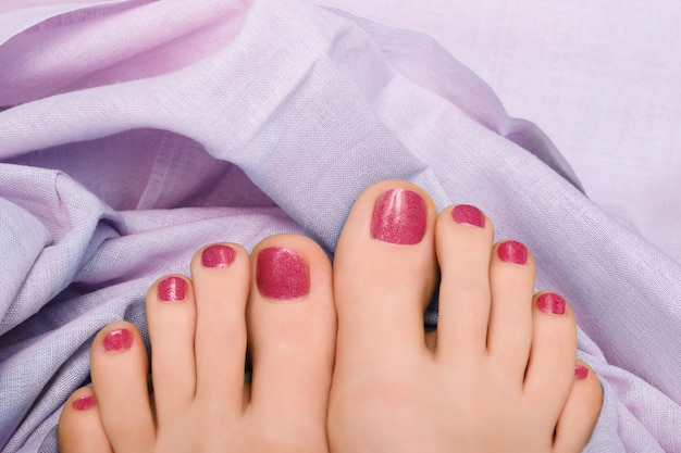 Beautiful female feet with pink glitter pedicure Free Photo