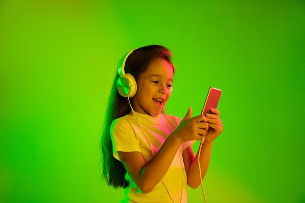 Красивый женский поясной портрет изолированный на зеленом backgroud в неоновом свете. молодая эмоциональная девушка. человеческие эмоции, концепция выражения лица. использование смартфона для видеоблога, селфи, чата, игр. Бесплатные Фотографии