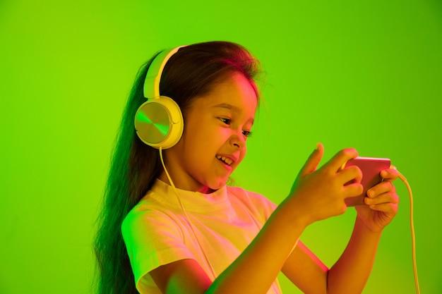ネオンの光の緑の壁に分離された美しい女性の半分の長さの肖像画。若い感情的な女の子。人間の感情、表情の概念。 vlog、selfie、チャット、ゲームにスマートフォンを使用する。 無料写真
