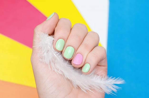 Beautiful female hand with light green and pink nail design Premium Photo